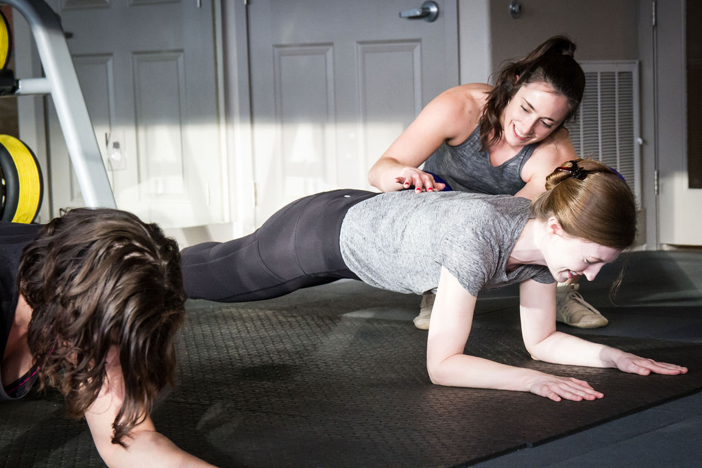 female personal trainer helping a woman with her exercise form