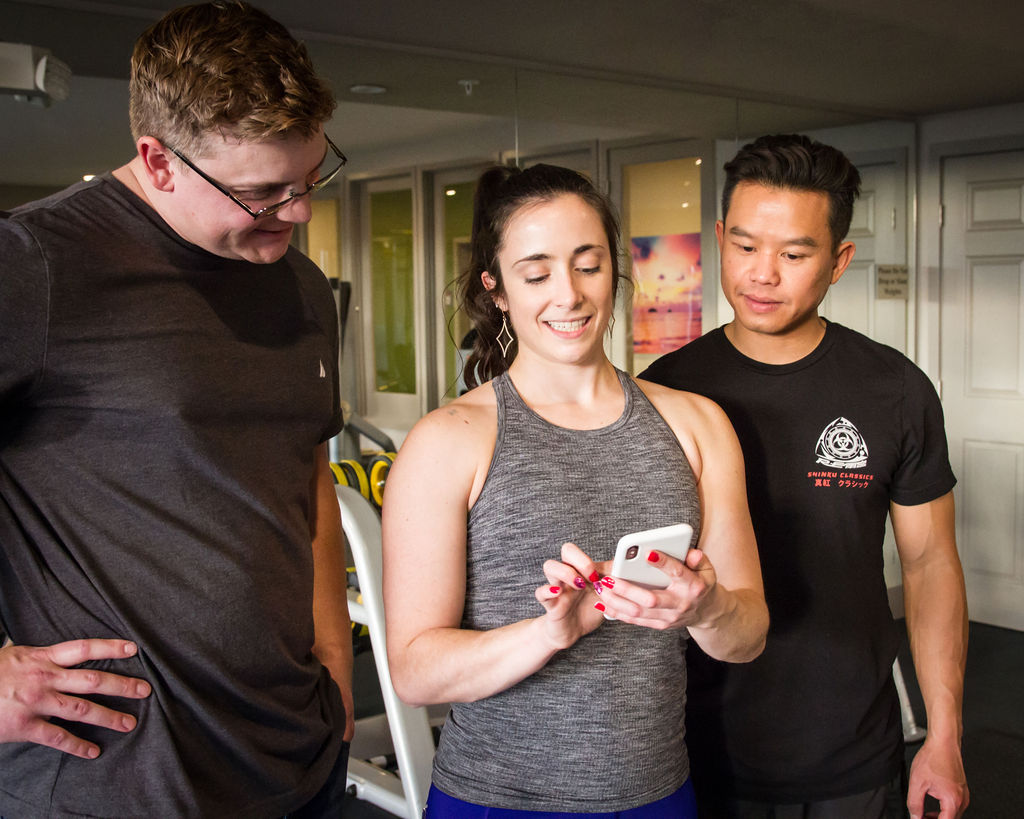 Two men in gym clothes smiling and looking at a Smartphone held by female fitness instructor